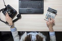 Femme d'affaires faisant des calculs et composant un numéro de téléphone Photographie stock