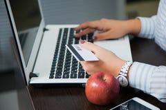 Femme d'affaires faisant des emplettes en ligne sur son espace de travail au bureau Images libres de droits
