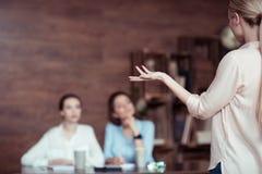 Femme d'affaires faisant des gestes et disant quelque chose aux collègues Images stock