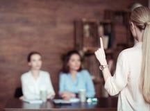 Femme d'affaires faisant des gestes et disant quelque chose aux collègues Images libres de droits