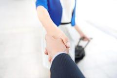 Femme d'affaires faisant la poignée de main avec un homme d'affaires à l'aéroport Image stock