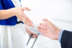 Femme d'affaires faisant la poignée de main avec un homme d'affaires à l'aéroport Photo stock