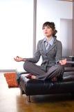 Femme d'affaires faisant le yoga dans un bureau moderne Image stock