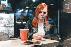 Femme d'affaires, fille tenant un stylo, ?crivant dans un carnet, ordinateur portable en caf?, smartphone, stylo, ordinateur d'ut image stock