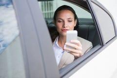 Femme d'affaires focalisée à l'aide de son téléphone Photographie stock