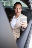 Femme d'affaires focalisée à l'aide de son téléphone Images stock