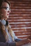 Femme d'affaires focalisée de hippie avec l'écouteur photo stock