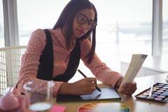 Femme d'affaires focalisée travaillant au convertisseur analogique-numérique au bureau image stock