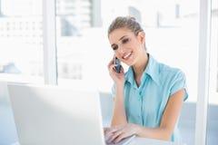 Femme d'affaires futée de sourire au téléphone tout en à l'aide de l'ordinateur portable Photos stock