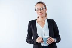 Femme d'affaires futée sérieuse tenant le café Photo stock