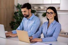 Femme d'affaires gaie à l'aide de l'ordinateur portable dans la cuisine photographie stock libre de droits