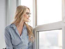 Femme d'affaires gaie détendant sur le rebord de fenêtre Photographie stock libre de droits