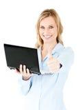Femme d'affaires gaie retenant un ordinateur portatif avec le pouce vers le haut Photographie stock libre de droits