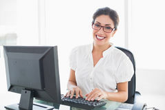 Femme d'affaires gaie travaillant à son bureau regardant l'appareil-photo Image libre de droits