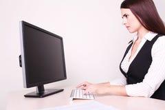 Femme d'affaires gaie travaillant à son bureau regardant l'appareil-photo dedans Photo stock