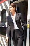 Femme d'affaires Getting Off Train à la plate-forme photo stock