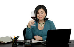 Femme d'affaires grillant un verre de vin rouge par conversation de Skype Photos stock