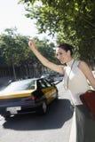 Femme d'affaires Hailing une cabine Image stock