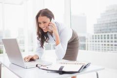 Femme d'affaires heureuse à l'aide de l'ordinateur portatif à son bureau Images libres de droits