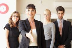 Femme d'affaires heureuse allant serrer votre main Image stock