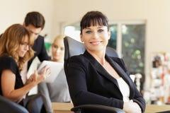 Femme d'affaires heureuse avec des collègues à l'arrière-plan Photo stock