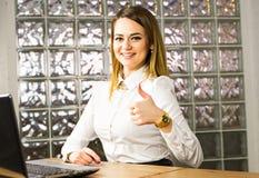 Femme d'affaires heureuse avec l'ordinateur portable montrant des pouces  Image stock