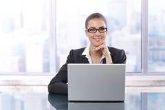 Femme d'affaires heureuse avec l'ordinateur portatif Image stock
