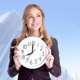 Femme d'affaires heureuse avec la grande horloge Photographie stock libre de droits
