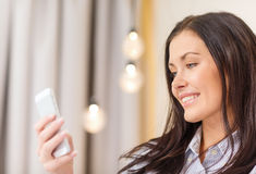 Femme d'affaires heureuse avec le smartphone dans la chambre d'hôtel Photographie stock libre de droits