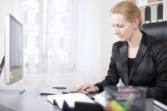Femme d'affaires heureuse Calculating à sa table de travail images stock
