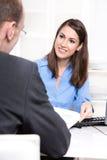 Femme d'affaires heureuse dans un chemisier bleu lors d'entrevue ou de réunion Image stock