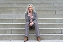 Femme d'affaires heureuse employant son mobile en ville image libre de droits