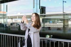 Femme d'affaires heureuse faisant le selfie par le smartphone près de la mallette et de l'aéroport Photo stock