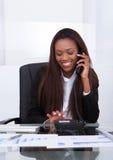 Femme d'affaires heureuse faisant un appel à partir de la ligne terrestre Photographie stock