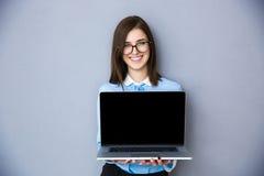 Femme d'affaires heureuse montrant l'écran vide d'ordinateur portable Photo stock