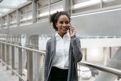 Femme d'affaires heureuse parlant sur le téléphone portable Photo stock