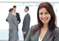 Femme d'affaires heureuse posant tandis que son parler d'équipe Image libre de droits