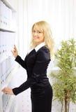 Femme d'affaires heureuse près d'étagère avec des dépliants Photographie stock