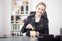 Femme d'affaires heureuse Putting Money sur la tirelire Photos stock
