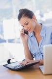 Femme d'affaires heureuse regardant son journal intime et appeler Photo libre de droits