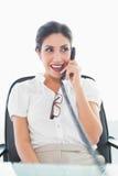 Femme d'affaires heureuse s'asseyant à son bureau au téléphone Photographie stock libre de droits