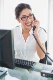 Femme d'affaires heureuse s'asseyant à son bureau parlant au téléphone Photo libre de droits