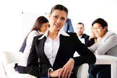 Femme d'affaires heureuse s'asseyant dans l'avant Photos stock