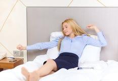 Femme d'affaires heureuse se situant dans le lit dans la chambre d'hôtel Photographie stock libre de droits