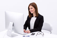 Femme d'affaires heureuse travaillant dans le bureau Photographie stock libre de droits