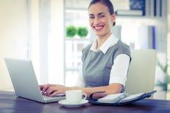 Femme d'affaires heureuse travaillant sur l'ordinateur portable et regardant l'appareil-photo Photo libre de droits