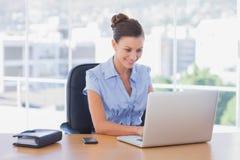 Femme d'affaires heureuse travaillant sur son ordinateur portable images stock