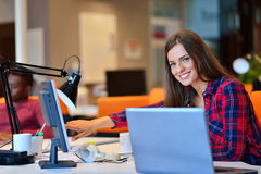 Femme d'affaires heureuse travaillant sur son ordinateur portable dans le bureau Images libres de droits