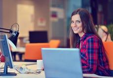 Femme d'affaires heureuse travaillant sur son ordinateur portable dans le bureau Images stock