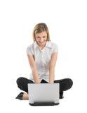 Femme d'affaires heureuse Using Laptop While s'asseyant sur le plancher Image libre de droits